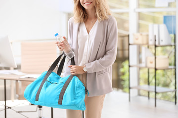 Young beautiful businesswoman holding fitness bag in office. Gym after work