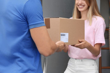 Young woman receiving parcel from courier on doorstep. Delivery service