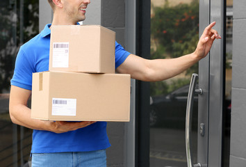 Delivery service courier with parcels in hands ringing doorbell outdoors