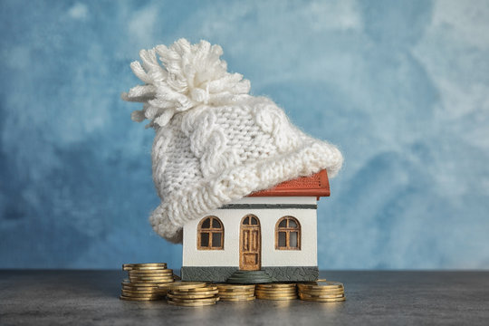 House model with knitted hat and coins on table against color background. Heating concept