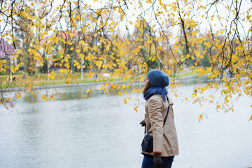 Cheerful  woman is walking in the park in autumn