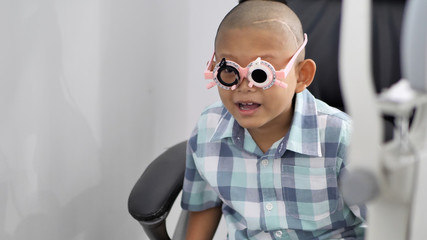 eyesight check. Asian boys who have vision disabilities. Left eye is not visible from brain surgery. Medical treatment and Rehabilitation..