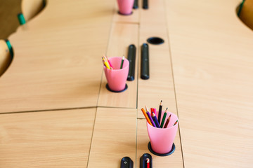 Color pencils in glass on desk with shallow depth of field Pencils in a glass on school desk