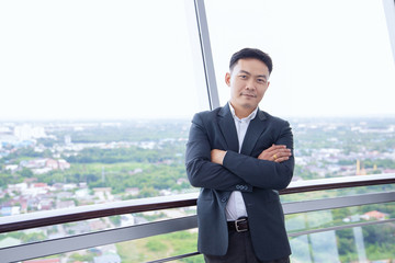 portrait of smiling chinese businessman with arms crossed on the top of building