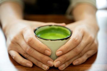 Hand holding a glass of green tea Japan.