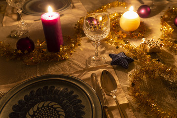 Detail view of a decorated dining table with burning candles, sterling cutlery, crystal glasses, colorful christmas balls and gold tinsel