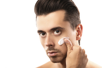 Young man is applying moisturizing cream on his face
