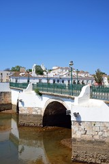 View of the Roman bridge (Ponte Romano) and Gilao river with town buildings to the rear, Tavira, Portugal.
