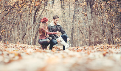 Woman and man petting the dog walking her in a colorful fall setting having fun in nature