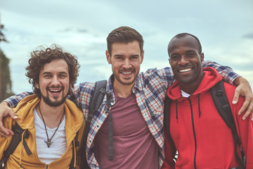 Diverse but together. Waist up portrait of positive guys making friendly embrace and smiling in front of camera