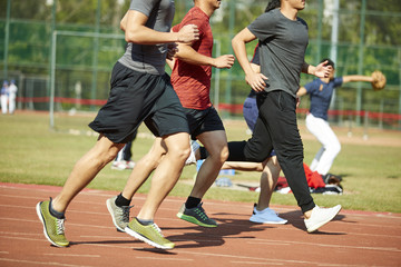 asian young adults running on track