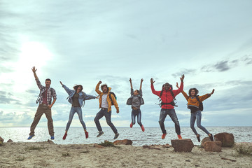Touching the sky. Full length portrait of joyful friends jumping at the seaside and holding their hands up