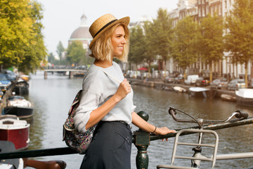 Happy traveler girl enjoying Amsterdam city. Smiling woman looking to the side on Amsterdam canal, Netherlands, Europe