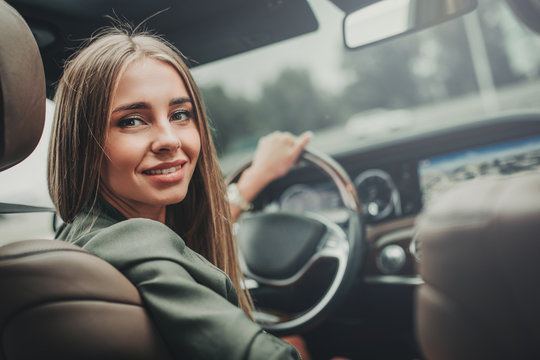 Portrait of optimistic pretty girl holding steering wheel while looking at camera. She locating in vehicle