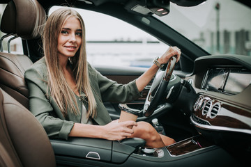 Portrait of smiling girl drinking mug of coffee while driving car. She holding steering wheel