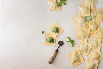 Homemade raw uncooked italian pasta ravioli staffed by spinach ricotta, basil leavrs, pasta cutter. White marble background. Flat lay, space