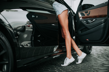 Close up long young lady legs in modern white trainers and sporty clothes locating near contemporary automobile