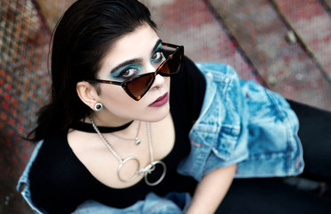 Young pierced woman wearing denim jacket and sunglasses