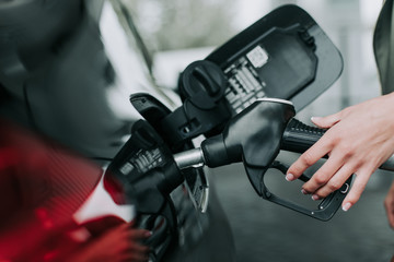 Close up female arm refueling the contemporary auto in petrol cap. She locating on filling station