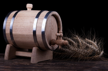 Wooden barrel with rye crops close up with black background