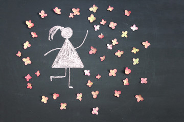 Chalk drawing woman icon surrounded by live pink flowers on chalkboard or blackboard. Women's day, feminism, girl power concept