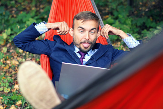 Businessman with laptop relaxs in a hammock on nature. He talking on video chat and doing funny faces with his tongue hanging out and splayed ears. Freelance or telework, on-line chatting concept