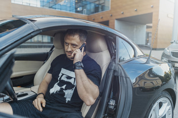 Man sitting behind the wheel of the black car and talking by mobile phone.