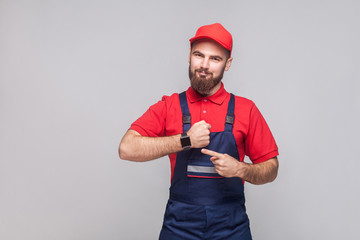 We do ontime. Young confident handyman with beard in blue overall and red t-shirt standing and showing time on his wrist watch with smile. Grey background, indoor, studio shot, isolated Wall mural