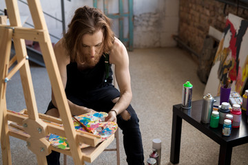 Portrait of handsome long haired artist sitting by easel in dim workshop looking for inspiration, copy space