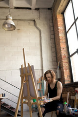 Portrait of handsome long haired artist painting on easel while working in dim art studio, copy space
