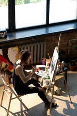 High angle view of handsome male artist painting on easel while enjoying work in sunlit art studio, copy space