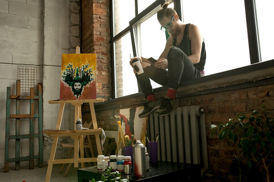 Wide angle portrait of contemporary male artist sitting on window in art studio and listening tio music via smartphone, copy space