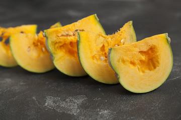 pumpkin, sliced pumpkin, bright orange pumpkin pieces on a dark background