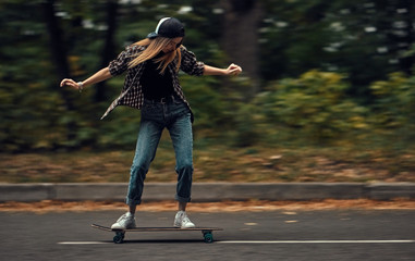 A girl on a skateboard is riding at high speed