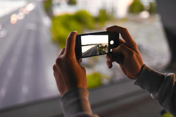 Close up of man's hands making a photo with smartphone in the street.