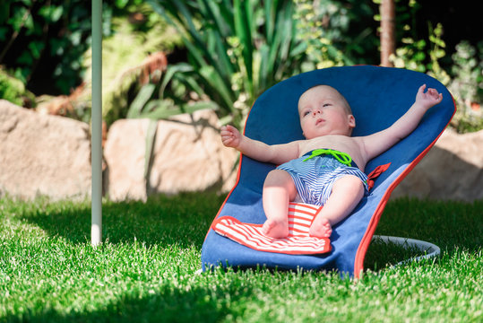Baby boy lies on a deck-chair on green lawn. Relax and vacation concept