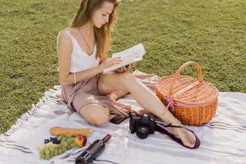 Top view of pretty young girl reading a book sitting on a green grass while having a picnic with wine and fruit in the parc. Hipster tourist blogger relaxing in the summer and enjoying holidays