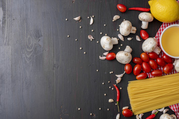 Spaghetti ingredients on black wooden desk, top view.
