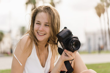 Pretty young girl laughing while taking pictures on professional dslr camera walking outdoors in the park on the summer sunny day, traveling, making photos, photography as a hobby, looking into camera