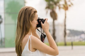 Female photographer with long hair taking pictures on professional dslr camera with the sky, grass and palm trees on the background, traveller making photos during summer vacation outdoors