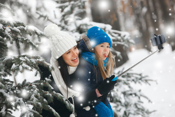 Young playful mother and her daughter making selfie outdoors in winter