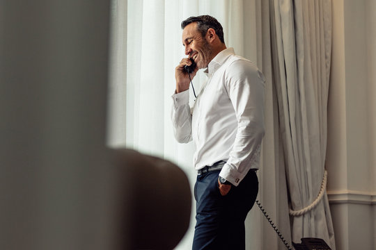 Businessman talking on phone from hotel room