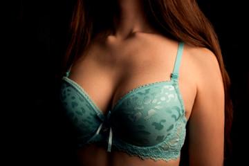 beautiful female breasts in a blue bra on black background