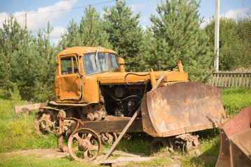 Old farm tractor in pines and fir trees before the fence