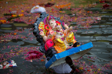 A devotee carries an idol of the Hindu god Ganesh, the deity of prosperity, to immerse it into a pond on the last day of the Ganesh Chaturthi festival in Ahmedabad