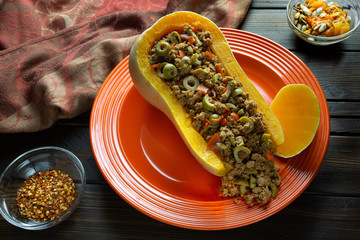 Fall colors with Butternut Squash Boat filled with ground beef with sliced olives on a red plate with some red pepper flakes on the side for a spicy kick on a wooden kitchen table.