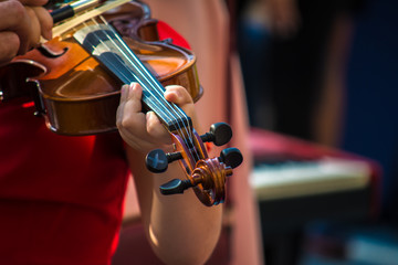 A young girl in a red dress is playing a violin. Street, sunny day. Close-up.