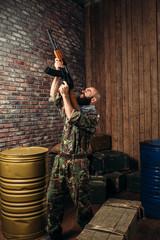 Bearded terrorist holding the kalashnikov rifle up