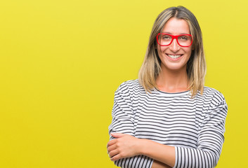 Young beautiful woman wearing glasses over isolated background happy face smiling with crossed arms looking at the camera. Positive person.