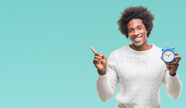 Afro american man holding vintage alarm clock over isolated background very happy pointing with hand and finger to the side